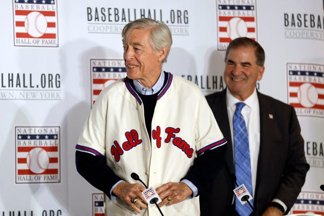 Former St. Louis Cardinals catcher Ted Simmons buttons a Hall of Fame jersey as National Baseball Hall of Fame President Tim Mead looks on, right, during the Major League Baseball winter meetings Monday, Dec. 9, 2019, in San Diego.