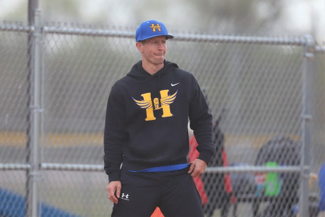 Hutchinson head softball coach Clayton Evans directs instructions at third base during an AVCTL game at the Fun Valley Sports Complex.