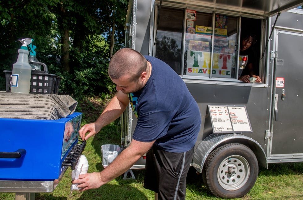 Peoria resident Alexander Payne tops shaved ice with a variety of flavors at the TMT Shaved Ice trailer on West Garden Street in Peoria.