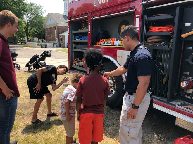 Newton firefigher Luke Edwards meets area children during SEAK, a program launched by Peace Connections of Newton to support children and families. Another new support for families started this week — the federal government making advance payments of a child tax credit.