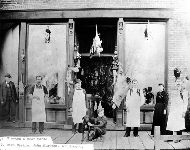 This photo shows the Slayton Meat Market on Tecumseh St. in Dundee, circa 1890. From left: Dave Martin, butcher; John Slayton, owner, and his son, Eugene Slayton, with his dog. The other two butchers are unidentified.