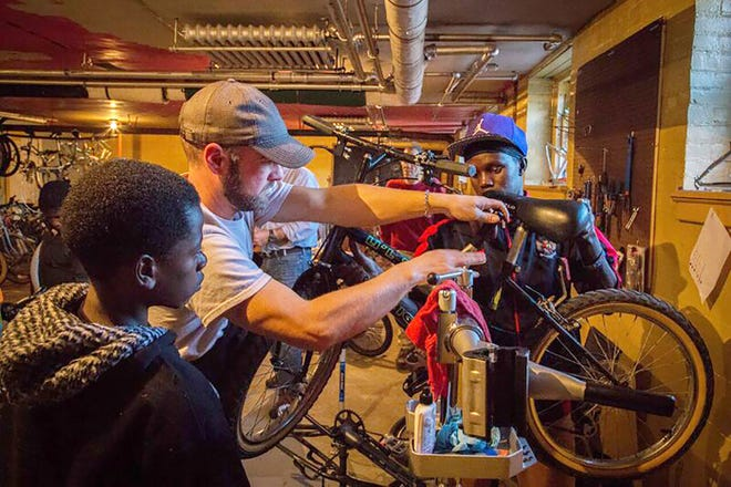 Matthew VanSlyke works on a bicycle at Utica Bike Rescue in May 2019. Utica Bike Rescue received $500 back in unclaimed funds Wednesday.