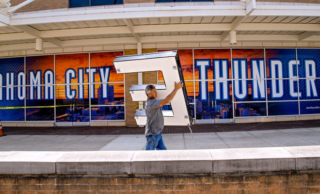 Kevin Parr, of Metro Sign Corporation, carries the letter 'E' as he works to remove the Chesapeake Energy Arena logo from the downtown arena.