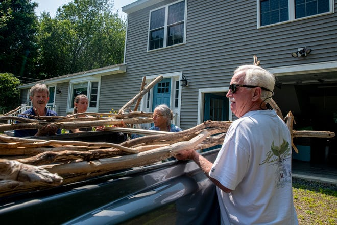David Pitney, far left, hauls a wedding altar arch made by Cherie Herne, center, owner of Salty Girl, in York, Maine on Thursday, July 15, 2021. Pitney and his friend Craig Lowry drove from East Windsor, Connecticut to pick up the altar for Pitney's daughter's wedding on Saturday.