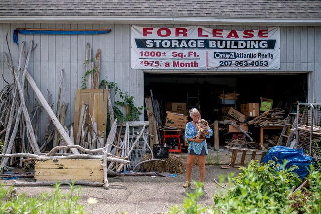 Cherie Herne, owner of Salty Girl, poses at her storage unit with her dog Piggie on Thursday, July 15, 2021 in York, Maine.