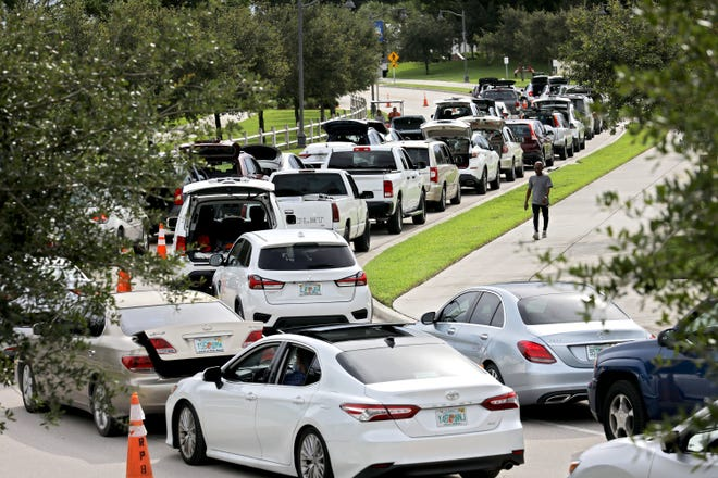 Cars line up for Royal Palm Beach's food distribution Wednesday at Commons Park, July 14, 2021.  Royal Palm Beach has hosted a food distribution every Wednesday since last April. It has given away nearly 1,500 tons of food to about 40,000 families.