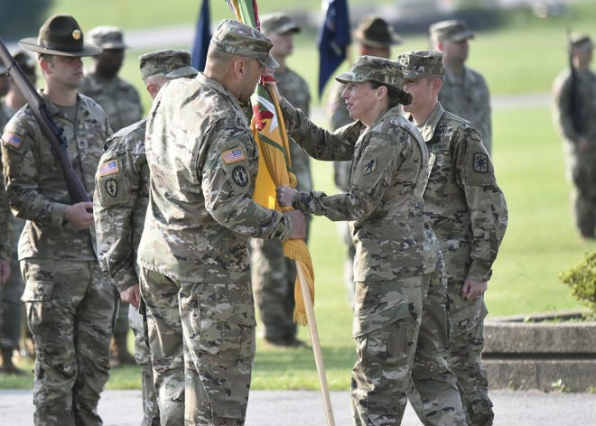Brig. Gen. Niave Knell, U.S. Army Military Police School commandant, passes the 14th Military Police Brigade colors to Col. Kirk Whittenberger during a change-of-command ceremony July 14 on Gammon Field. Photo by Brian Hill, Fort Leonard Wood Public Affairs Office