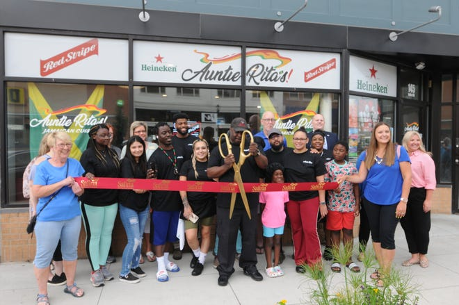Kavelle Gordon, owner of Auntie Rita's, cuts the ribbon in front of his new downtown location.