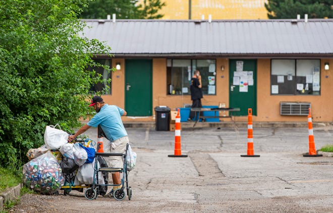 A resident attaches bags of aluminum cans to a shopping cart in a parking lot at the Knights Inn, which is currently being used as part of the Motels 4 Now program to house homeless people, on Thursday, July 15, 2021, in South Bend.