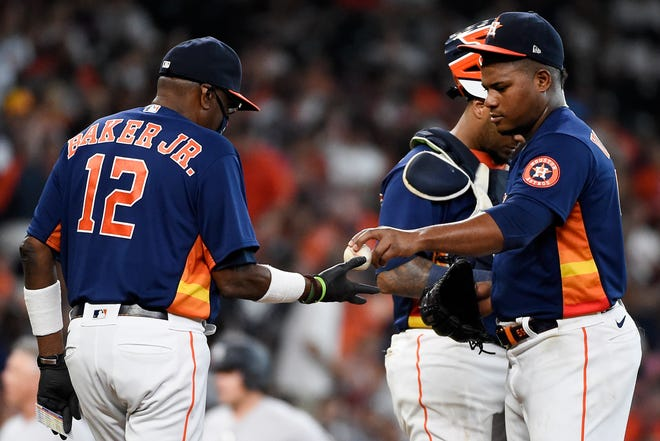 Houston Astros starting pitcher Framber Valdez, right, his removed by manager Dusty Baker Jr. (12) during the fifth inning of a baseball game against the New York Yankees, Sunday, in Houston.