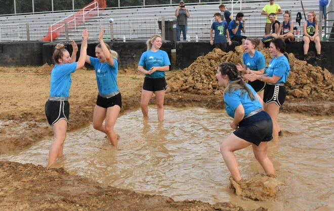 """""""The Queens"""" made up of 2021 Owen County Fair Queen court members and contestants celebrates as they score a point in mud volleyball in the main arena. More photos from the event are featured on today's SEW."""