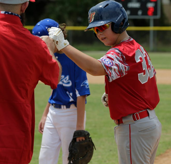 Noah Zachodny of the Sarasota 13-year-old All-Stars receives a fist bump from first base coach Mason Johnson during the opening-round win over Weston.