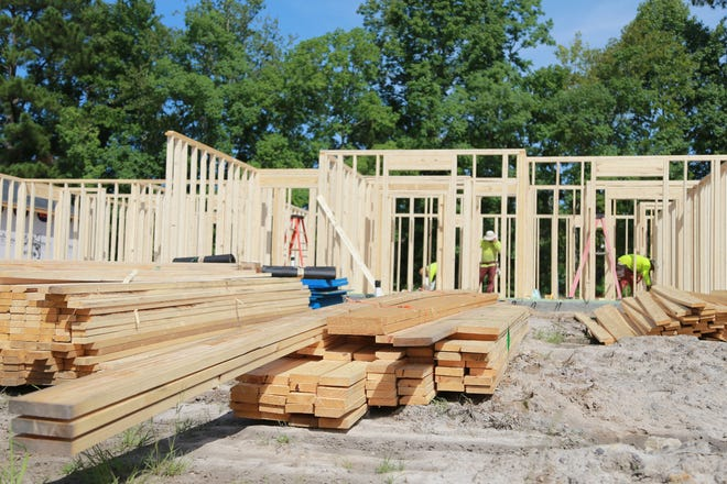 Framers work at a new home being built off Cottonvale Road. Construction costs are on the rise, mainly due to the cost of lumber supplies.