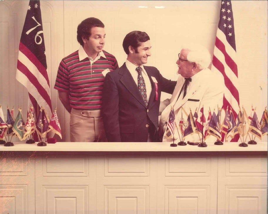 Οι ιδιοκτήτες franchise Ralph M. Potter (αριστερά) και Steve Paris μιλούν με τον ιδρυτή της KFC, συνταγματάρχη Harland Sanders το 1976.