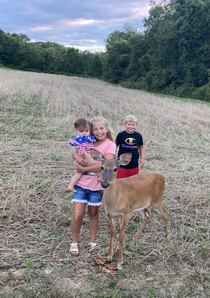 Caroline Cottrell, 9, Cole Cottrell, 7, and Lena Warner, 11 months, are shown with the male deer that has befriended them in Uhrichsville. Caroline and Cole are the children of Veronica Cottrell. Lena is her granddaughter.