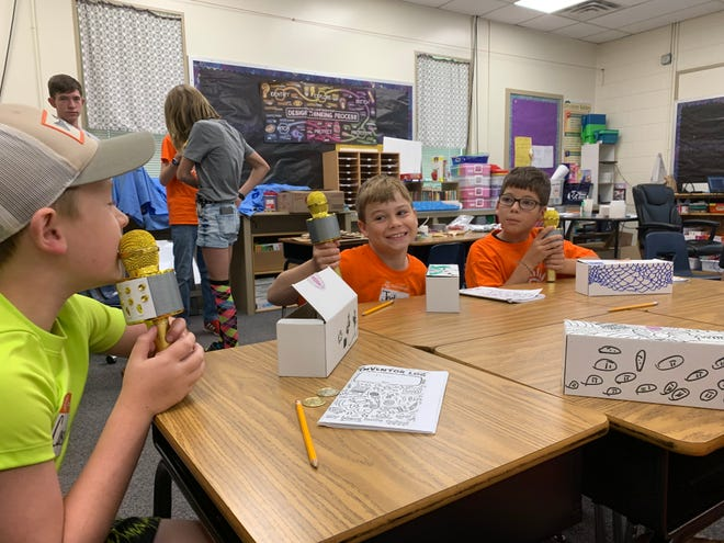 Camp Invention participants getting ready to use their microphones during Open Mic on Wednesday morning. Students get a chance to reverse engineer a wireless microphone during the session.