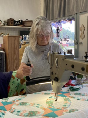 Ladonna Brahler hand guides a long-arm quilting machine at  Let's Sew in Magazine.