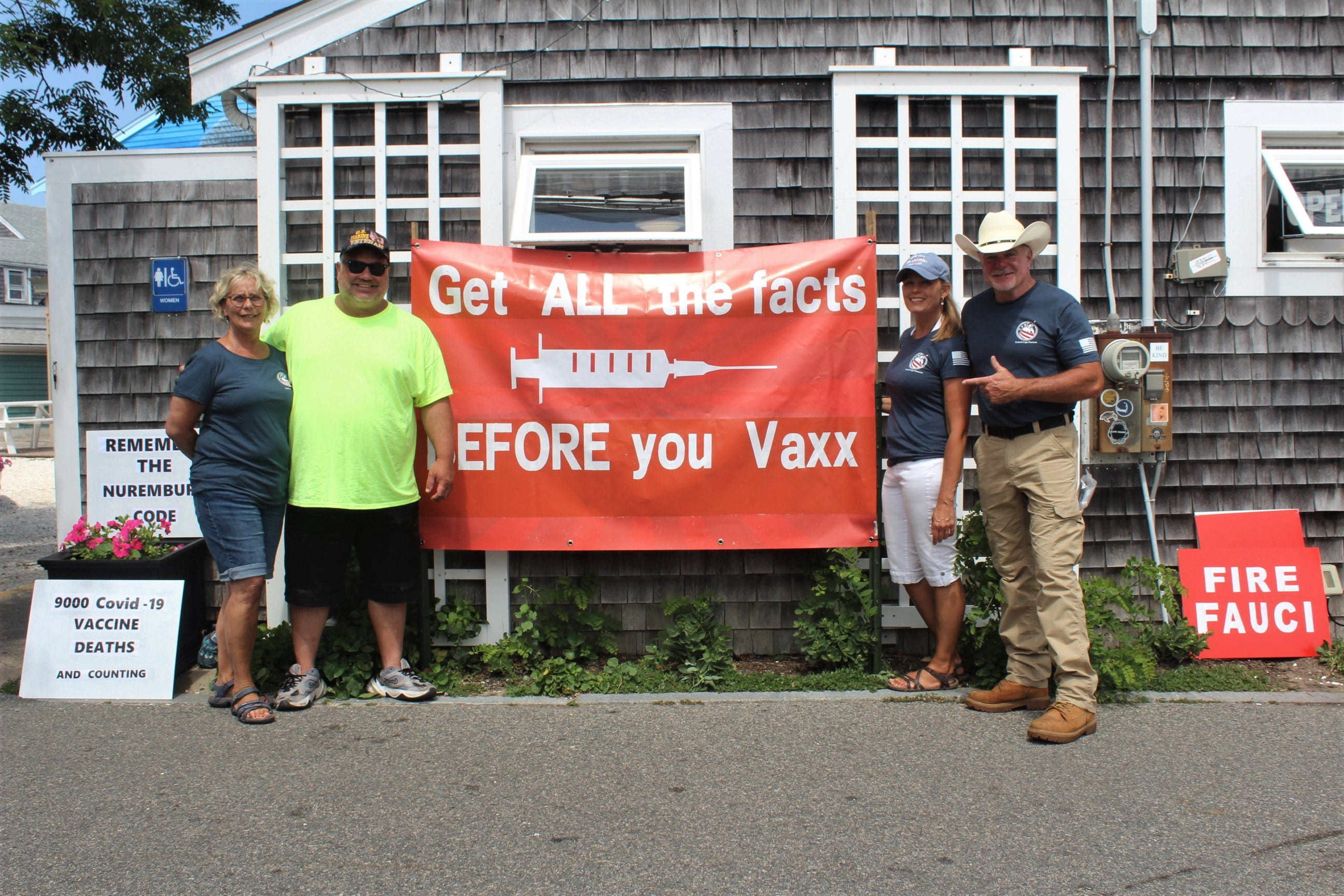 """Four people of the grass-roots conservative group, United Cape Patriots, stand outside the state's VaxBus handing out flyers.   """"We're not anti-vax, we're about freedom,"""" said United Cape Patriots founder Adam Lange."""