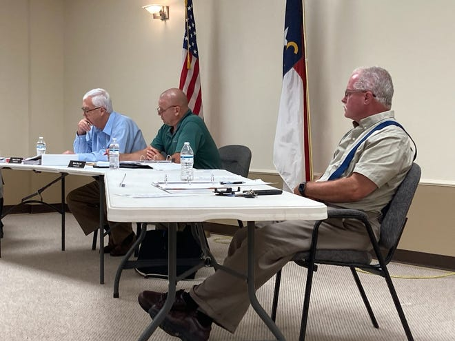 From left, Interim County Manager Norris Gentry, Chair Mark Snelson and Commissioner Craig Goforth hear public comments during Madison County Board of Commissioners' July 13 meeting.