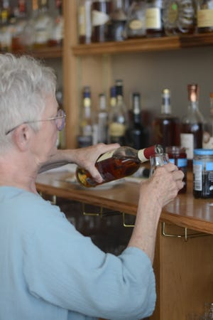 Brenda Coates, owner of the Brandy Bar, pours a drink for a customer.