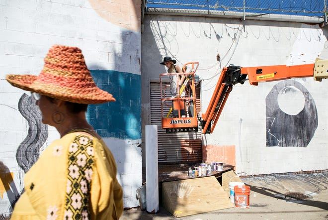 Detroit artist Ellen Rutt works on a mural at the 2018 edition of Murals in the Market in Detroit's Eastern Market.