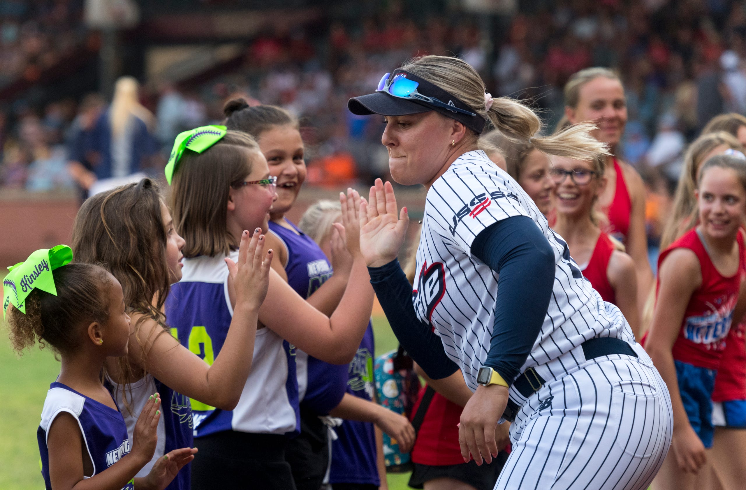 USSSA Pride's Amanda Lorenz (18) runs down the line giving high fives to the Newburgh Nitro softball team ahead of the exhibition game between USSSA Pride and Team Florida at Bosse Field in Evansville, Ind., Wednesday evening, July 14, 2021.