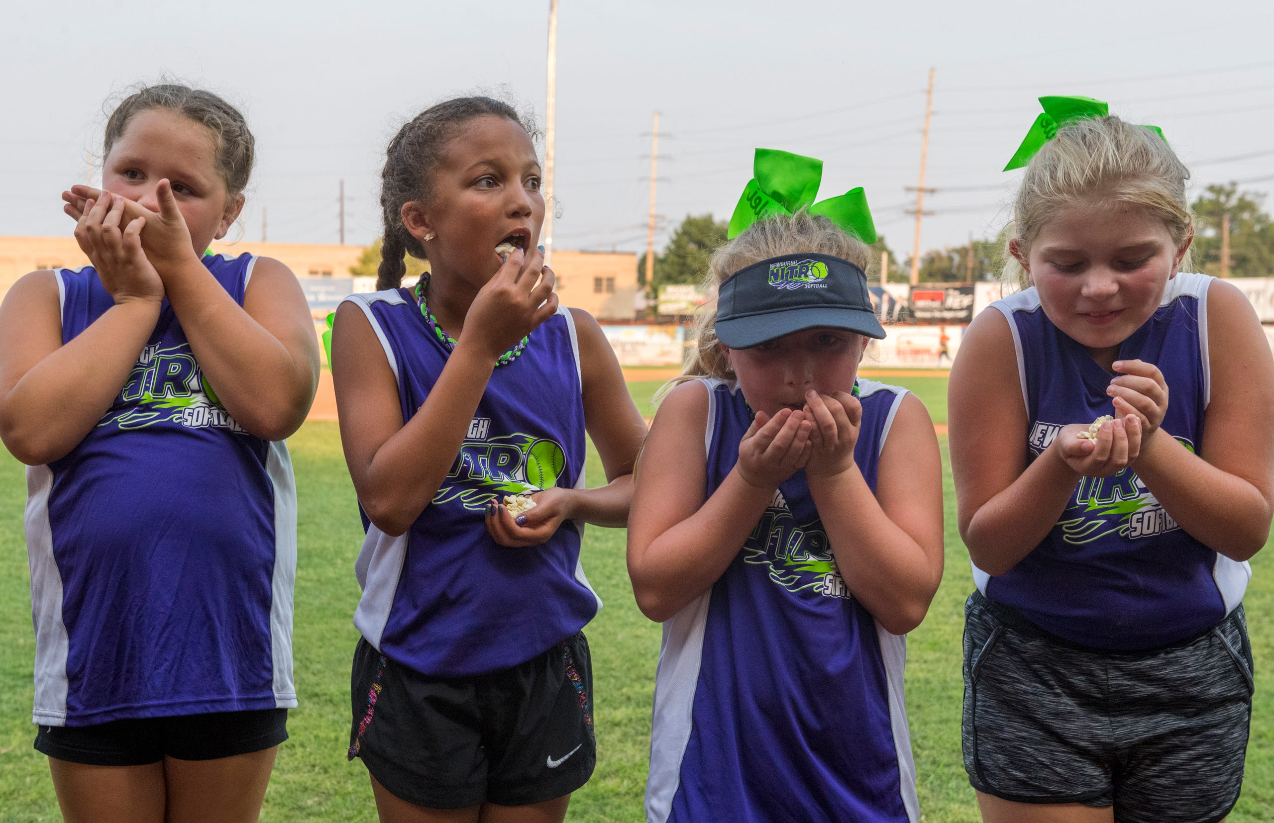 The Newburgh Nitro softball team eats popcorn on the field ahead of the exhibition game between USSSA Pride and Team Florida at Bosse Field in Evansville, Ind., Wednesday evening, July 14, 2021.