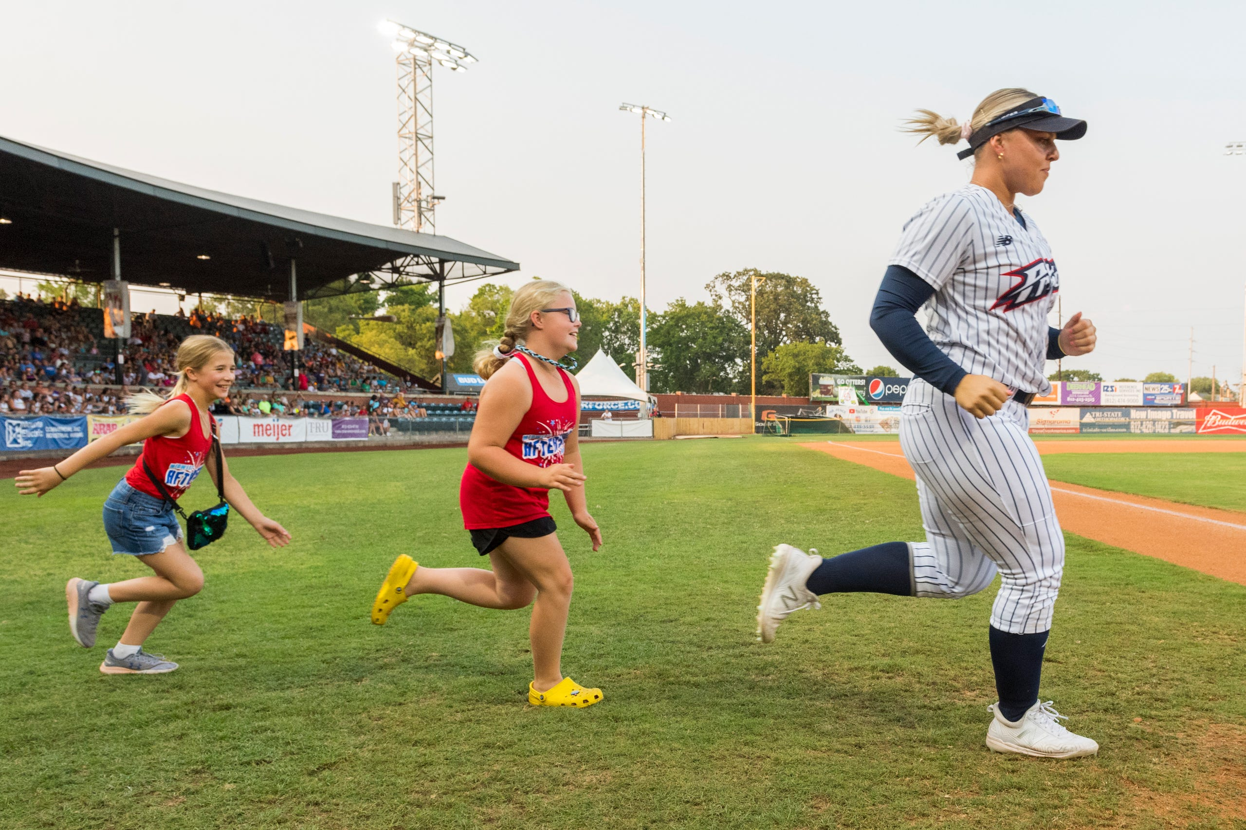 USSSA Pride's Amanda Lorenz (18) is followed onto the field by Midwest Aftershock's Kaylie HaberKamp, left, and Emma Bottcher, center, ahead of the exhibition game between USSSA Pride and Team Florida at Bosse Field in Evansville, Ind., Wednesday evening, July 14, 2021.