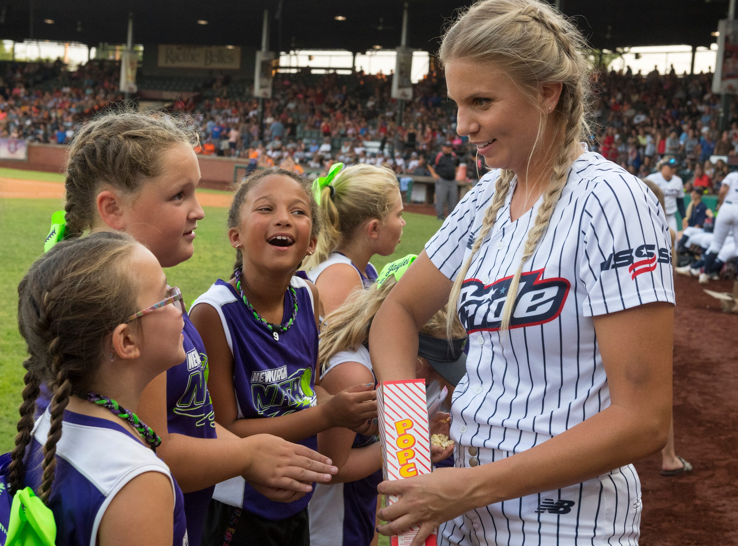 USSSA Pride's Jessica Burroughs (16) hands out popcorn to the Newburgh Nitro softball team ahead of the exhibition game between USSSA Pride and Team Florida at Bosse Field in Evansville, Ind., Wednesday evening, July 14, 2021.