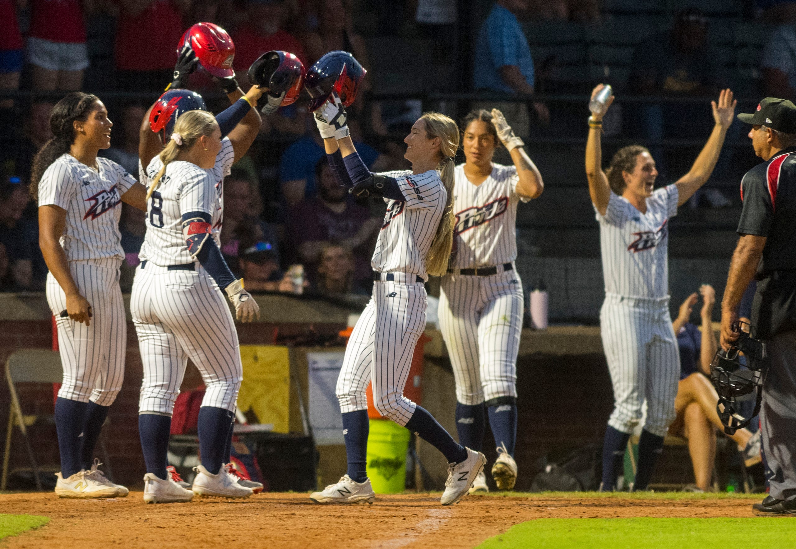 USSSA Pride team celebrates USSSA Pride's Haley Cruse (10) after a home run hit during their exhibition game against Team Florida at Bosse Field in Evansville, Ind., Wednesday evening, July 14, 2021.