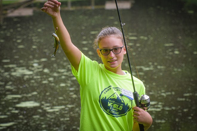 Sixth grader Makaylee Meagher holds the second blue gill she caught at Oak Openings during Camp Wildcats.