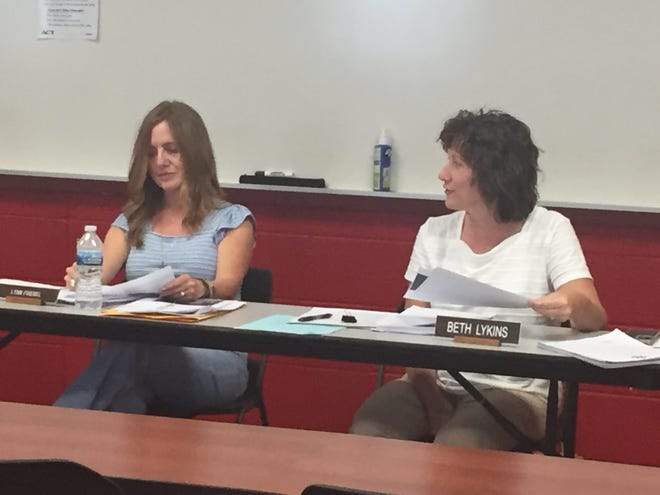 Shelby City Schools treasurer Beth Lykins makes a point at Thursday's board meeting. Board member Lynn Friebel looks on.