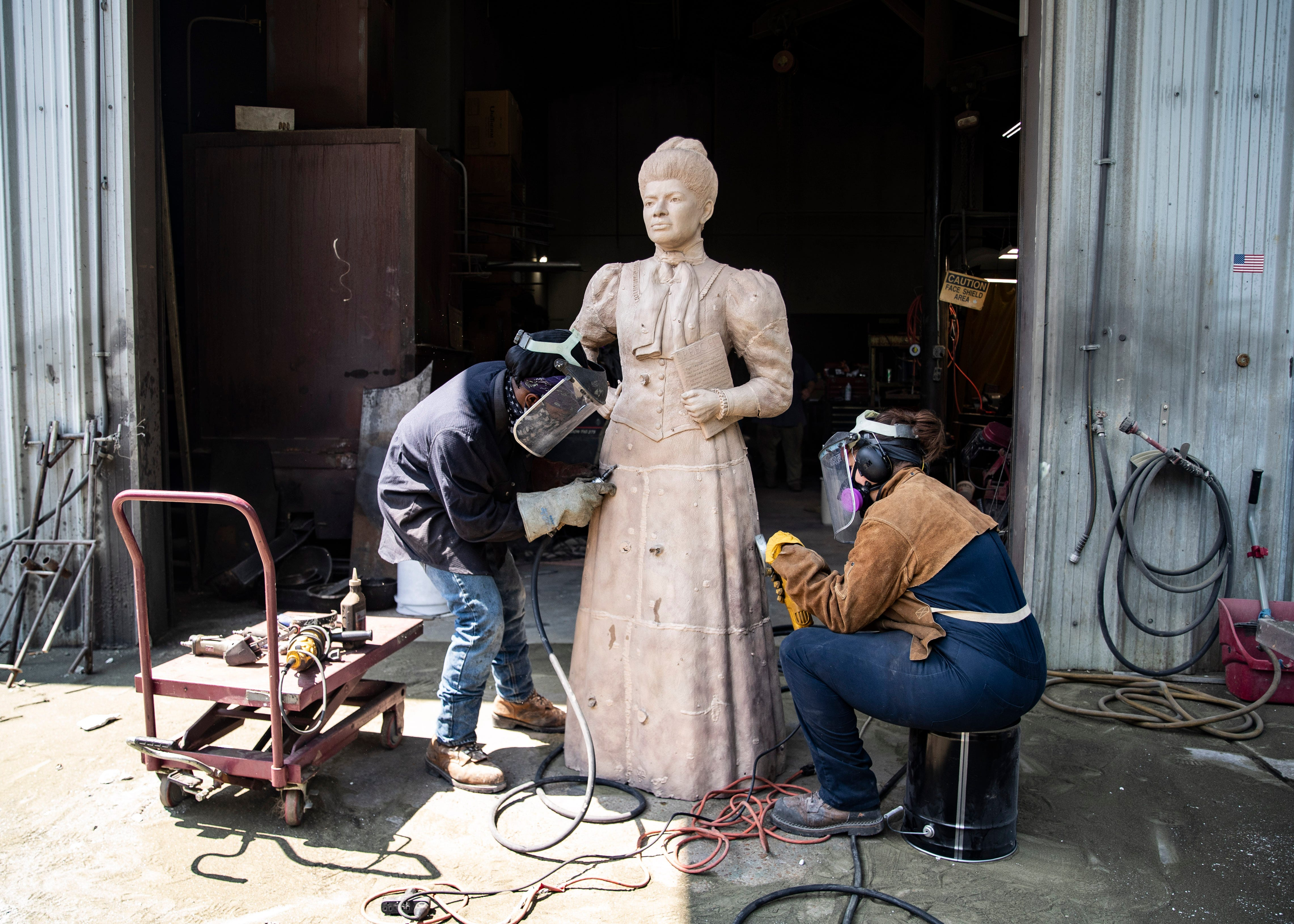 Artisans Terrance Payne and Marda Mesler use drills during the bronze chasing process to create the statue of  Ida B. Wells-Barnett, the African American civil rights advocate and journalist who fought against racism, segregation and lynching, at the Lugar Bronze Foundry in Eads, Tenn., on Tuesday, May 26, 2021.