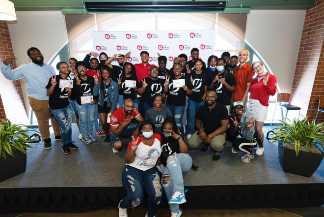 Indianapolis Colts running back and UW Credit Union brand ambassador  Jonathan Taylor takes a group photo with youths from Urban Underground following a talk on financial literacy in the SKYY lounge at American Family Field on July 1.