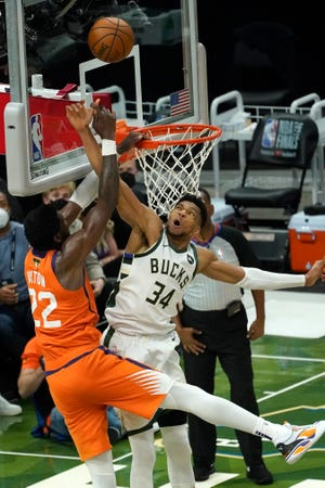 Giannis Antetokounmpo blocks a shot by Phoenix center Deandre Ayton, preventing the Suns from tying the game with the clock winding down in Game 4.
