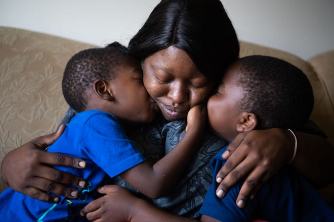 Courtney Strickland hugs her children, 4 and 5, as they kiss her on the cheek in their home in Smyrna, Tenn., Thursday, July 15, 2021.