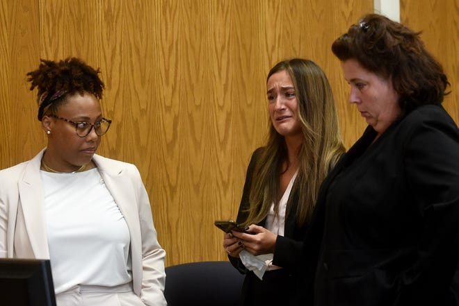 Kalina Gillum (center) cries while speaking of the intimate partner abuse she survived while standing before Licking County Common Pleas Court Judge David Branstool with attorneys Yveka Pierre (left) and Cassandra Mayer.