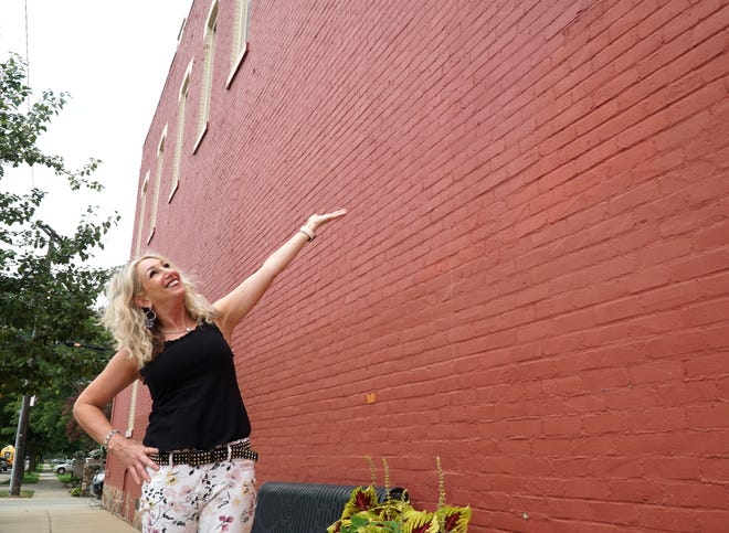 Grande Trunk owner Susan Stowe shows where on her building at 101 N. Lafayette artist Kevin Burdick will paint a mural in the coming months.