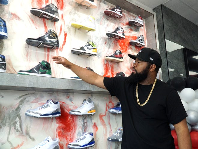 Privileged Kicks owner Darrell Harrison shows off some of his Westland store's display of Nike and Air Jordan shoes.