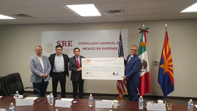 Leaders with the Mexican Consulate of Phoenix and the CEO of Friendly House pose for a picture with the $15,500 check they donated to Mexican college students in need.
