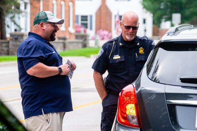 St. Clair City Councilman and Murphy Inn Manager Mitch Kuffa and St. Clair Police Chief Timothy Raker talk to a person pulled over for following the speed limit while handing out gift cards Thursday, July 15, 2021, in St. Clair. St. Clair Police Department and local businesses partnered to hand out gift cards to people following the law.