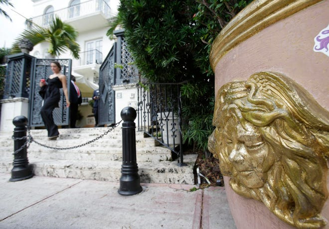 FILE - In this Sept. 17, 2013, file photo, the Versace logo is shown on a planter outside of the South Beach mansion that once belonged to Gianni Versace in Miami Beach, Fla. Two men apparently killed themselves, police said, Thursday, July 15, 2021, in a suite at the Miami Beach hotel that Gianni Versace turned into his mansion, nearly 24 years to the day before the fashion designer died on the building's front steps. Their bodies were found by housekeeping on Wednesday, the eve of the anniversary of Versace's slaying by a suspected serial killer.  (AP Photo/Wilfredo Lee)