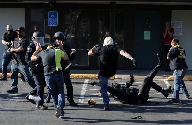 Salem Police officers move to break up a fight as individuals in Proud Boys attire kick a downed member of an antifascist group during a protest at Planned Parenthood in Salem Tuesday.
