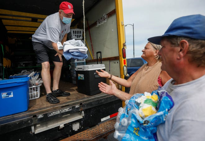 Jerry Scott, left, of the Connecting Grounds, hands sheets over to Tim Coffelt and Christina Flowers on Thursday, July, 15, 2021. The Connecting Grounds closed due to the COVID-19 outbreak and was out delivering supplies to members of the homeless community.