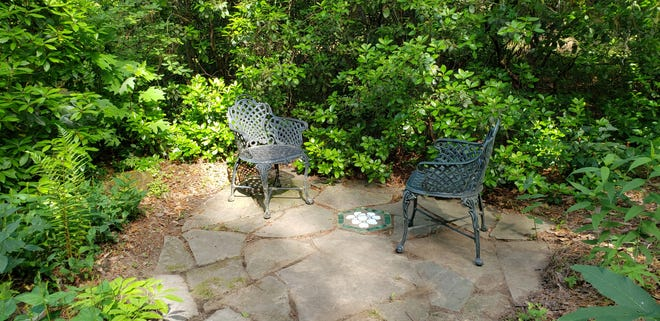 Two chairs and a small patio is all you need for this secret garden.