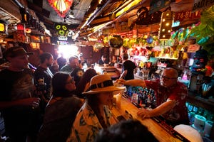 Patrons enjoy cold tropical cocktails in the tiny interior of the Tiki-Ti bar as it reopens on Sunset Boulevard in Los Angeles, July 7, 2021. Los Angeles County public health officials have urged people to resume wearing masks indoors regardless of their vaccination status.