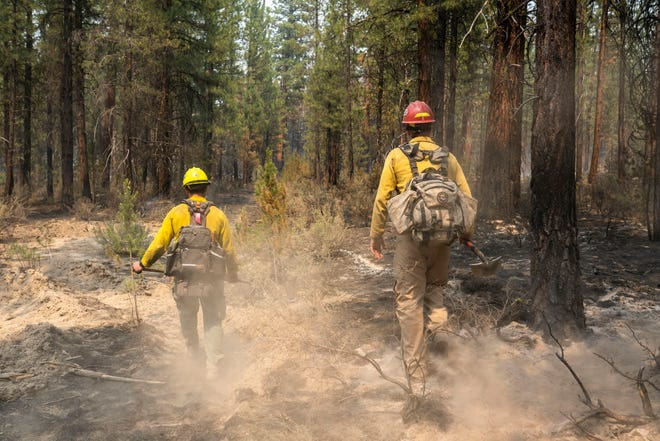 Firefighters Garret Suza, right, and Cameron Taylor, with the Chiloquin Forest Service, search for hot spots on the North East side of the Bootleg Fire, Wednesday, July 14, 2021, near Sprague River, Ore.