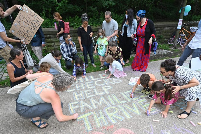 Parents and children celebrate new monthly Child Tax Credit payments and urge congress to make them permanent outside Senator Schumer's home on July 12, 2021 in Brooklyn, New York.