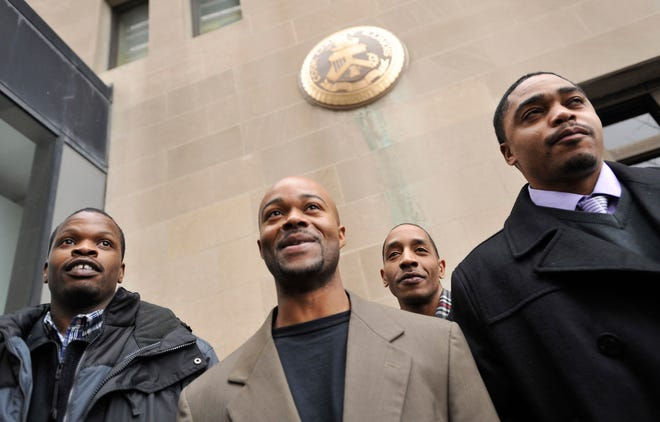 """Harold Richardson, left, Vincent Thames, second from left, Terrill Swift, and Michael Saunders, right, pose for a photo on Jan. 17, 2012, after a hearing in Chicago for the four men known as """"the Englewood Four,"""" whose 1994 rape and murder convictions were overturned in November 2011."""