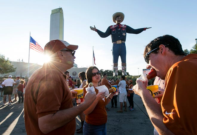 """OCTOBER 10, 2015 -  Texas fans, Mark Jacobs, Jennifer Bowland, Billy Jacobs, behind, and Ryan Jacobs, left to right, enjoy a famous Fletcher's corndog in front """"Big Texas"""" at the State Fair of Texas before the start of the Big 12 conference game between Texas and Oklahoma held at the Cotton Bowl in Dallas, Tx., on Saturday, October 10, 2015.   (RODOLFO GONZALEZ / AMERICAN-STATESMAN)"""